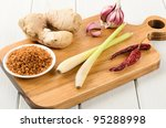 Oriental ingredients on a wooden chopping board: Clockwise, starting from the far left: roasted dessicated coconut, ginger, garlic, dried chillies and lemongrass. - stock photo