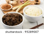 Beef Rendang & Sticky Rice - Malaysian/Indonesian spicy dry beef stew served sticky rice. Main dish ingredients on the chopping board (roasted desiccated coconut, ginger and garlic, lemon grass). - stock photo