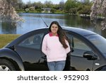 female teen outdoors leaning on car posing at an urban pond - stock photo