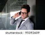 Portrait of handsome man in office building talking on phone - stock photo