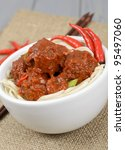 Chinese Spicy Meatballs - Chinese spicy pork meatballs in fragant tomato sauce served with noodles. - stock photo
