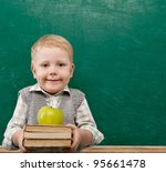 Cheerful smiling child with a book and apples stands at the blackboard . Looking at camera. School concept - stock photo