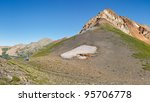 Hiker resting at pass below Rolling Mountain in the San Juan Range along the Colorado Trail. - stock photo