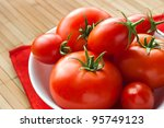 fresh tomatoes in white bowl on red napkin - stock photo