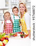 Education for a healthy diet - kids with their mother in the kitchen - stock photo