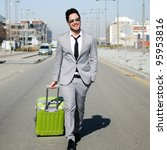Man dressed in suit and suitcase in the street - stock photo