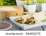 Peking Duck - Chinese peking duck wrapped in pancakes with cucumber, spring onions and hoisin sauce. - stock photo