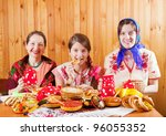 Women in traditional  clothes eats pancake with tea during  Shrovetide - stock photo