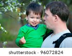 Father and his little son talking outdoors in spring park - stock photo