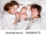Happy family with newborn baby on bed - stock photo