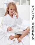 Little girl with a bad case of influenza using nasal spray and a box of paper tissues - stock photo