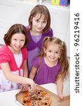 Young girls having pizza for snack - stock photo