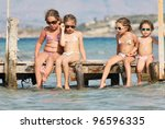 Children on the wooden pier by the sea - stock photo
