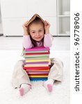 Little girl with lots of books having fun - stock photo