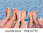 Children legs on the wooden pier above the sea - stock photo