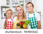 Happy people with healthy food in the kitchen - stock photo