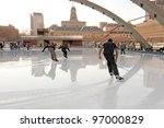 TORONTO, CANADA - MAR 7: Skaters skate through large puddles of water covering the ice at the City Hall outdoor rink during near record high temperature for March 7, 2012 in Toronto, Ontario, Canada. - stock photo