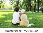 Stock photo teenager boy in the park with a golden retriever dog 97043852