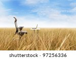 Outdoor office in a golden grass with a clear blue sky - stock photo
