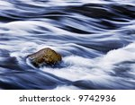 Water Rushing By A Rock In A...