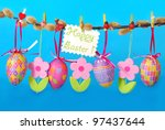 easter border with hanging colorful eggs and  felt flowers against blue background - stock photo