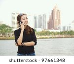 Young pretty Asian calling by phone with building background - stock photo