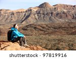 Hiking - woman hiker enjoying view. Woman sitting looking over beautiful volcano mountain landscape. From volcano Teide, Tenerife, Canary Islands, Spain. - stock photo