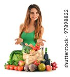Young caucasian woman with groceries including fruits, vegetables and wine isolated on white - stock photo