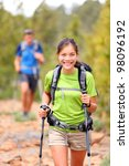 Hiker woman. Hiking asian woman walking with hiking poles and hiking backpack smiling happy outdoors in nature. Hiker in background. - stock photo