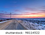 Winter road at sunset near wind turbines field - stock photo