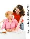 Small photo of Teen girl helping senior woman fill out absentee ballot. Isolated on white.