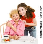 Small photo of Teen girl helping her grandmother fill out an absentee ballot. Isolated on white.