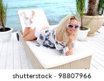 Young attractive woman lie on a lounger on sea beach. - stock photo