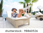 Young attractive woman in hat lie on a lounger on sea beach. - stock photo