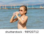 Girl drinking water on the beach - stock photo