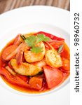 Thai style sweet and sour shrimp dish presented beautifully on a round white plate. - stock photo