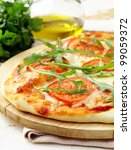 Margarita pizza with tomatoes and with arugula,  on the board - stock photo