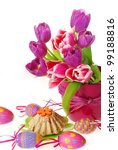easter decoration with painted eggs,ring cake and bunch of purple tulips in vase isolated on white - stock photo