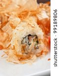 Sushi rolls of rice, nori, cream cheese, avocado, smoked salmon,cucumber and cuts of tuna - stock photo