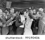 Kissing couple surrounded by men with guns - stock photo