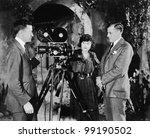 Three people with movie camera - stock photo