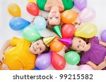 Party kids and their mother laying among colorful balloons - stock photo