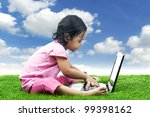 Adorable girl playing game on the laptop computer. Shot under clear sky - stock photo