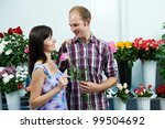 Man presenting flower to girl at shop on a date - stock photo