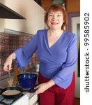 Mature woman cooking pancake at her kitchen - stock photo