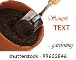 Clay flower pot with potting soil and spade on white background with copy space. - stock photo