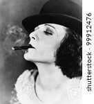 Portrait of a young woman with a hat smoking a cigar - stock photo