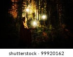 Fantasy scene with a caped woman in a forest with glowing balls of light created with texture layers. - stock photo