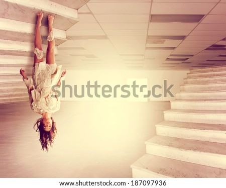 a beautiful woman defying gravity in a large empty warehouse done with a warm vintage instagram filter  - stock photo