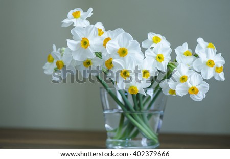 A bouquet of white daffodils in a glass vase on a wood table